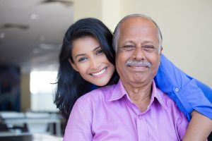 young woman in blue shirt holding older man in pink collar button down from behind, happy isolated indoors home background